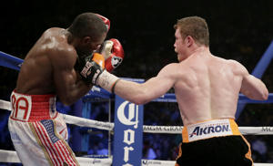 Canelo Alvarez, right, of Mexico, lands a punch on …